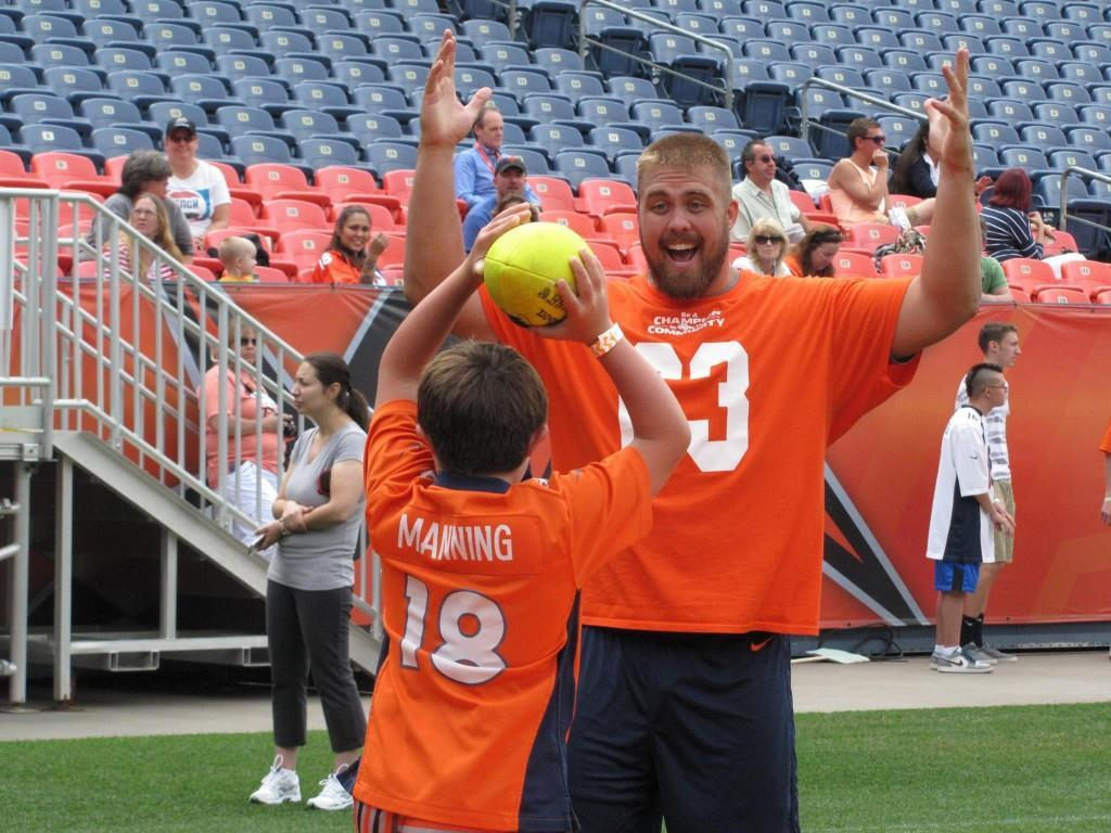 Broncos player Ben Garland makes a human goal post for an NSCD athlete. Credit.