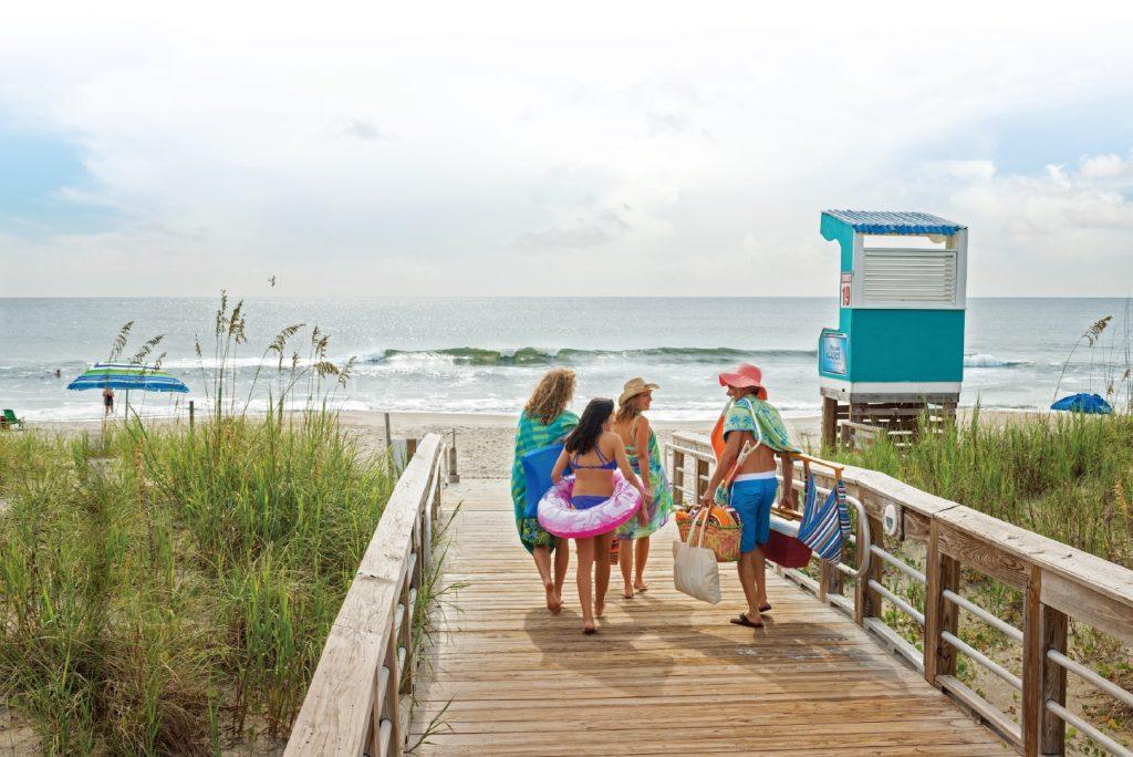A Carolina beach family on the boardwalk. Photo courtesy of Wilmington and Beaches CVB